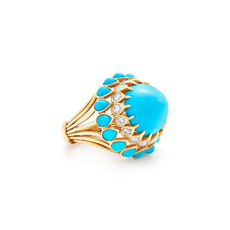 Set with a central cabochon turquoise (not quite a sugarloaf), within a round diamond gallery to the bezel-set pear-shaped cabochon turquoise frame to the reeded shoulders, mounted in 18k gold, circa 1960s Signed Cartier, Paris  Total weight of the