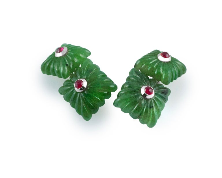 "These exquisite cufflinks are made entirely of jade and feature a squared front face and a smaller, identically shaped toggle, both made of jade with the traditional ""fesonato"" texture. The center of each square is highlighted with a cabochon ruby"