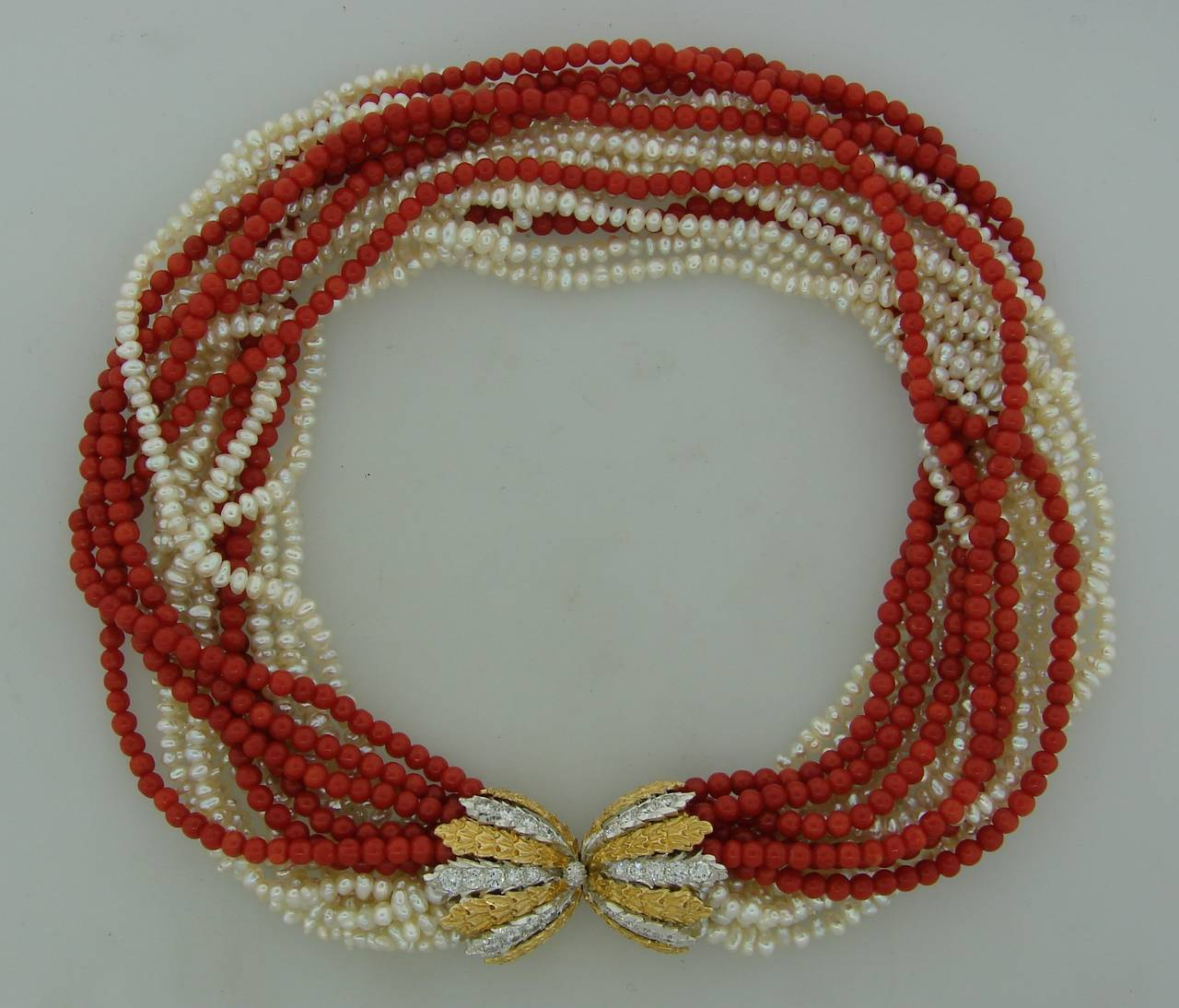 Fabulous elegant necklace created by Mario Buccellati in Italy in the 1950's. Features ten strands of white freshwater pearls and six strands of Mediterranean coral connected with a diamond and yellow & white gold clasp. The necklace has a lot