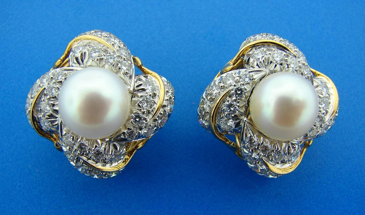 Classy and timeless clip-on earrings created by Jean Schlumberger for Tiffany & Co. in the 1970's. Feature a beautiful white Akoya pearl surrounded with round brilliant cut diamonds set in 18k yellow and white gold. Diamond total weight is