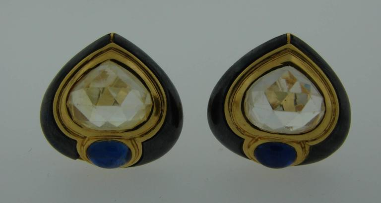 Bold yet elegant colorful clip-on earrings created by Bulgari in the 1980's. Made of 18k yellow gold and hematite and feature rose cut light yellow sapphire and cabochon blue sapphire.  The earrings are clip-on, posts can be added.  They measure 7/8