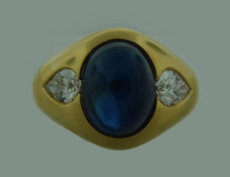 Classy and timeless cocktail ring created by Bulgari in the 1970's. Features 6.05-carat cabochon  sapphire set in 18k (stamped) yellow gold and accented with pear shape diamonds. The diamond total weight is approximately 1.04 carats, they are F-G