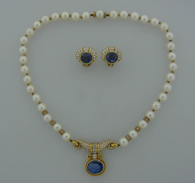 Elegant and timeless set consisting of a necklace and a pair of earrings. Created by Bulgari in Italy in the 1980's. Features thirty seven Akoya pearls, oval faceted blue sapphires set in 18k yellow gold and accented with round brilliant and