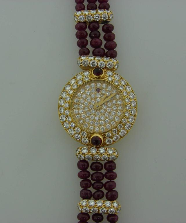 Elegant dressy lady's watch created by Boucheron Paris in the 1980s. It is made of 18 karat (stamped) yellow gold, the face is encrusted all over with round brilliant cut diamonds and the bracelet is made of ruby beads and diamonds set in yellow