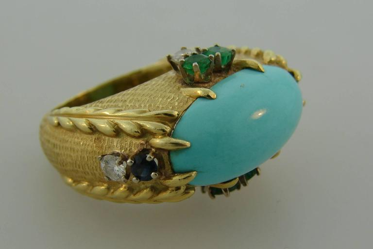 Stunning cocktail ring created by Cartier in New York in the 1970's. It features a beautiful oval-shaped Persian turquoise set in 18 karat yellow gold and accented with round brilliant cut diamonds, round faceted emeralds and sapphires. Unusual