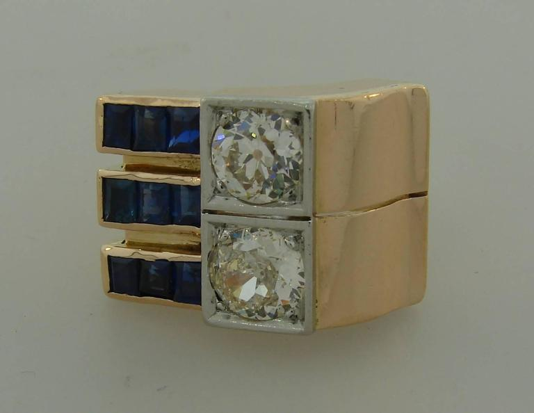Bold and smart retro ring created in the 1940s. It features two Old European cut diamonds accented to one side with three rows of pre-cut table cut sapphires. The diamonds are approximately 0.98-carat (K color, VS2 clarity) and 1.10-carat (M color,