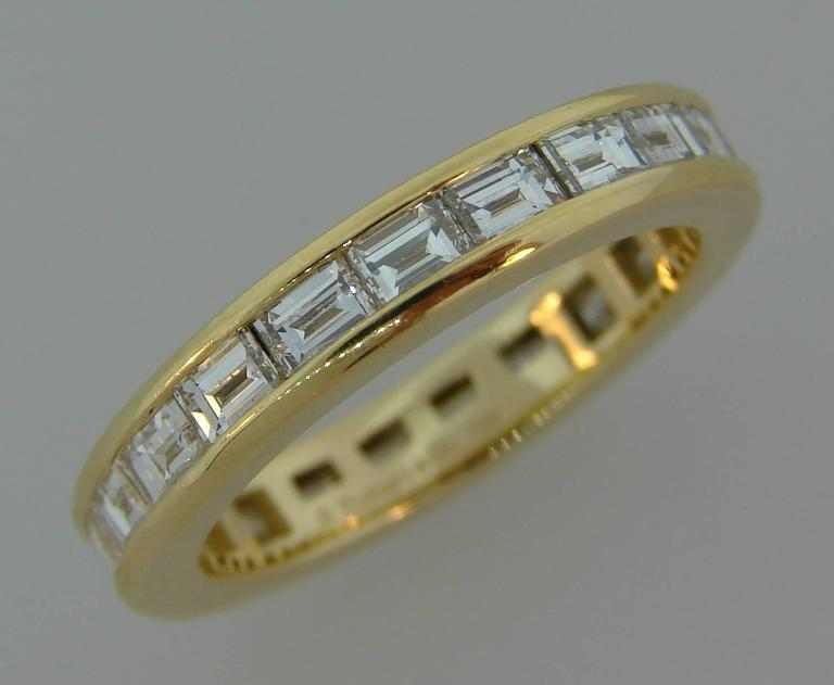 Classy and timeless eternity band created by Tiffany & Co.  It is made of 18 karat yellow gold and twenty one horizontally set baguette cut diamonds (F-G color, VS1 clarity, total weight approximately 2.10 carats).  The band is size 5.5. It is