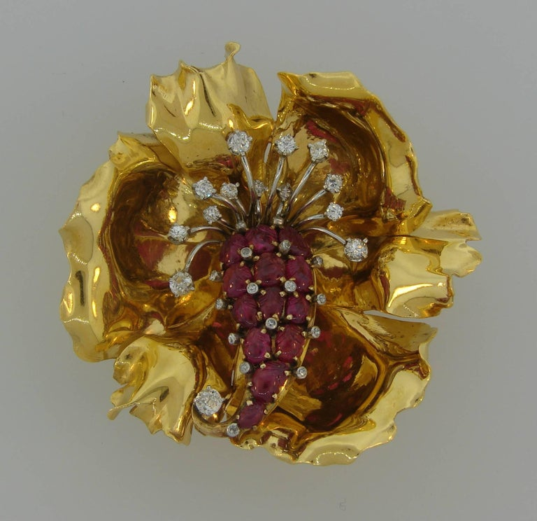 Gorgeous three-dimensional flower clip. Chic accent to any outfit, the brooch is a great addition to your jewelry collection.  Made of 18 karat (stamped) yellow gold and set with thirteen carved rubies and accented with thirty Old European cut