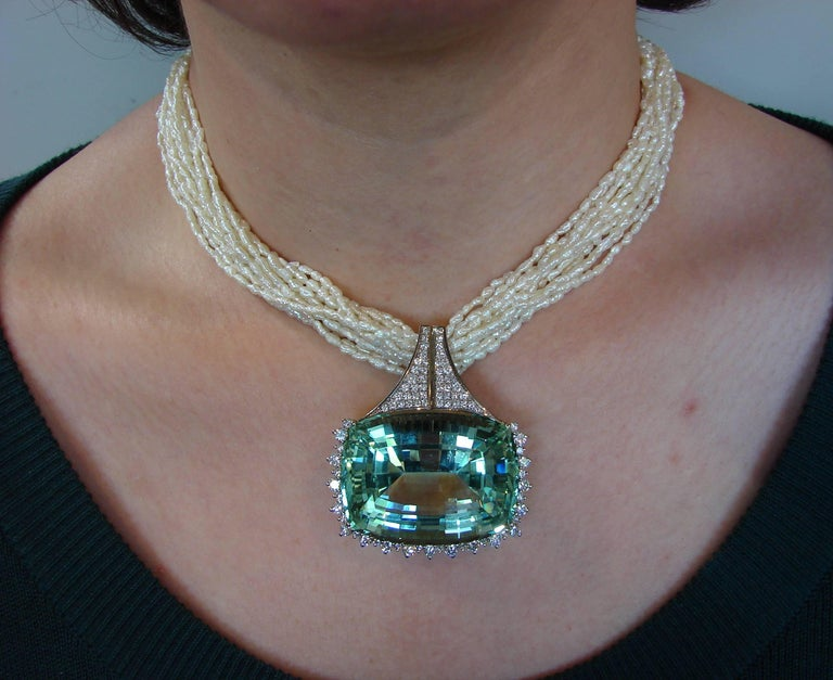 Magnificent 160.70-carat cushion cut Brazilian aquamarine set in diamond and 18 karat white gold pendant on a multi-strand freshwater pearl necklace finished with a diamond and 18 karat white gold clasp. The aquamarine has amazing slightly greenish