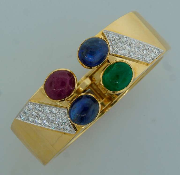 Chic and wearable cuff bracelet created by David Webb in the 1970's. Bold yet elegant! Features a ruby cabochon, an emerald cabochon and two sapphire cabochons set in yellow gold and accented with round brilliant cut diamonds. The diamonds are set