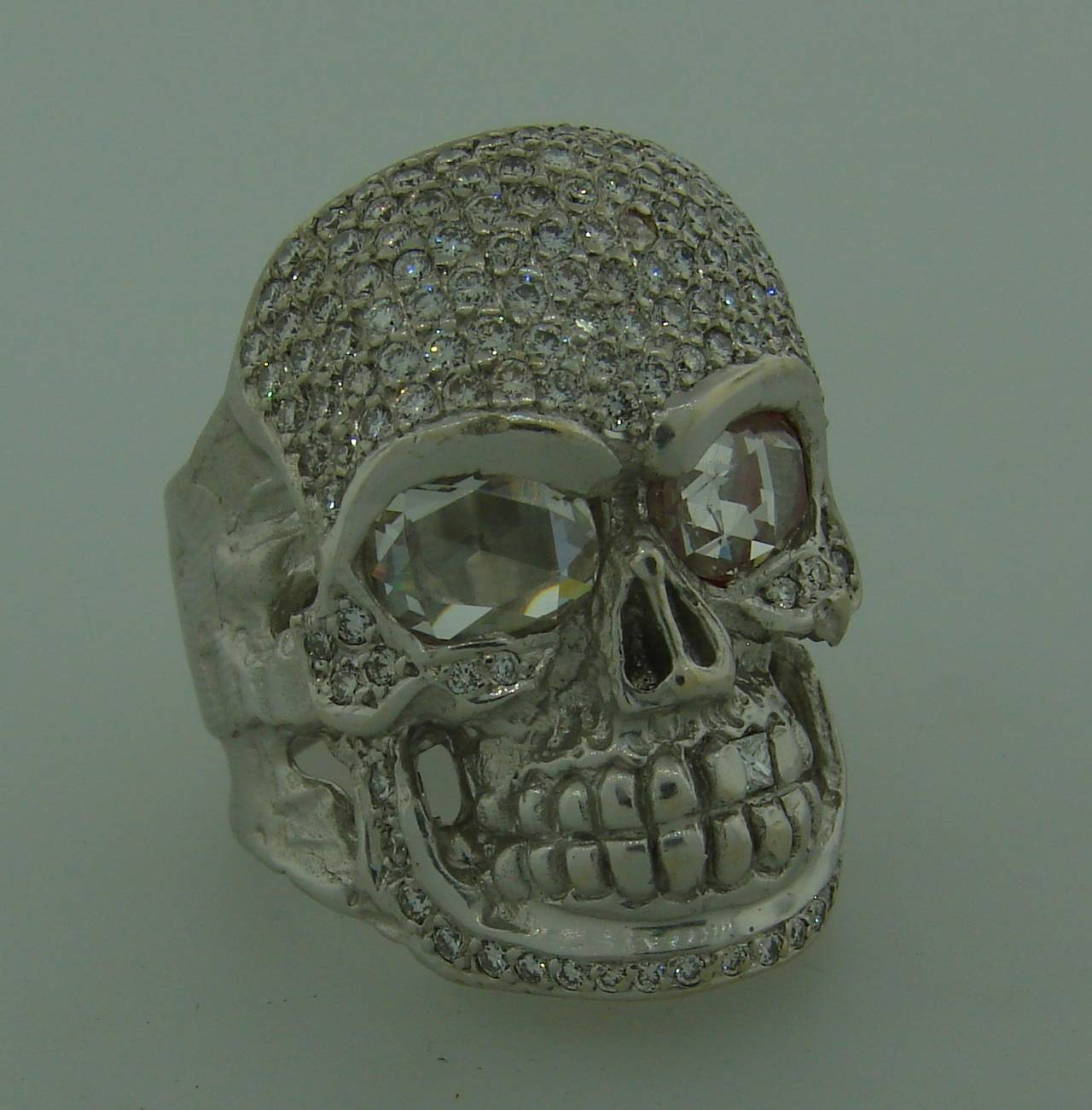 Outstanding diamond skull ring created by a renown Hollywood designer Loree Rodkin. Features two rose cut diamonds as the skull's eyes, round brilliant cut diamonds all over the face and one princess cut diamond as its tooth.  The rose cut diamonds