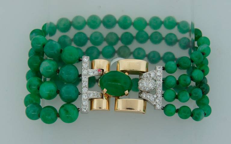 Fabulous jade bead bracelet created in the 1940's. Features four strings of graduating jade beads finished with a diamond and yellow gold clasp. The beads are graduating from 8.0 to 5.1 mm. The clasp is made of 14k yellow gold, set with
