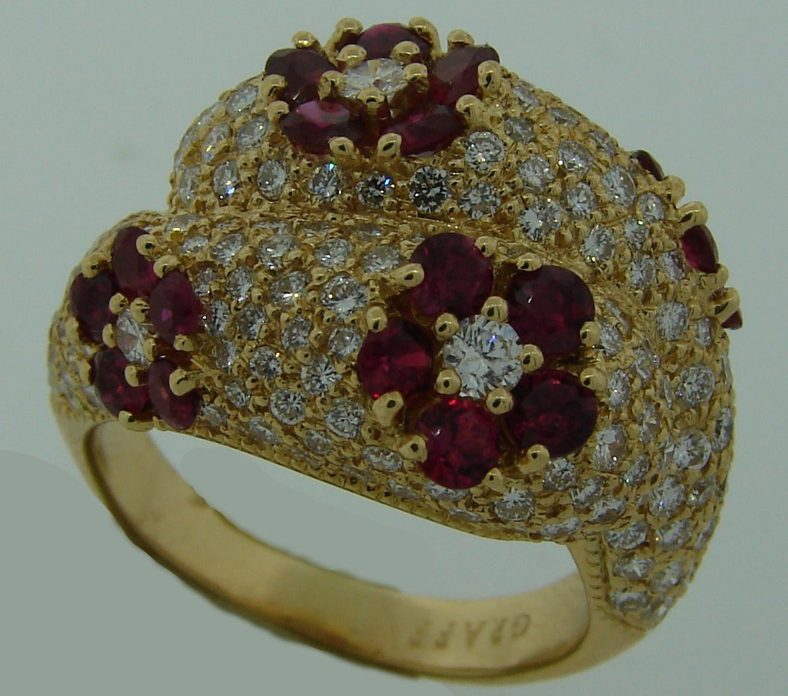 Chic and feminine cocktail ring created by GRAFF in the 1980's. Features four ruby flowers in a diamond pave field set in 18k yellow gold.