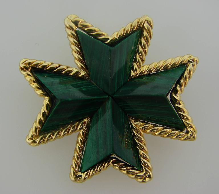 Colorful and elegant Maltese cross pin created by Tiffany & Co. in Italy.  It is made of 18 karat (stamped) yellow gold and carved malachite.  The pin measures 1-3/8 x 1-3/8 inches and weighs 18.4 grams.  Stamped with Tiffany & Co. maker's