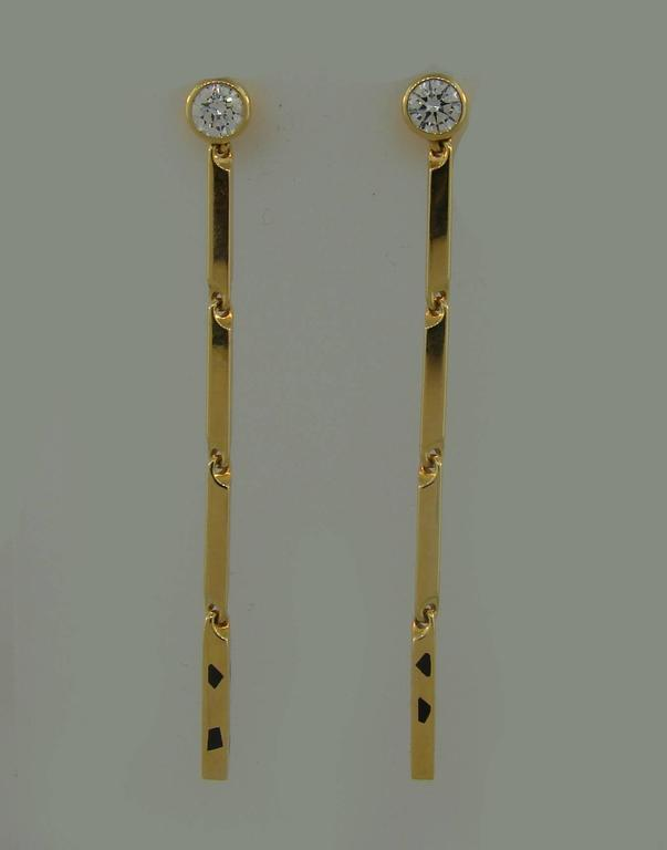 Popular Cartier Panthere Collection pair of earrings that is a great addition to your treasure box.  The earrings are made of 18 karat yellow gold and accented with a round brilliant cut diamond and black enamel.  They are 2.25 inches (5.6 cm) long,