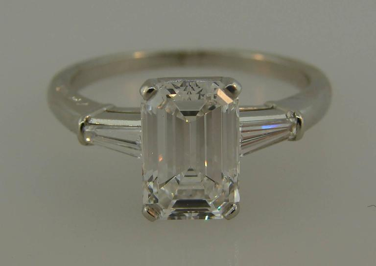 "Stunning engagement ring created by Cartier. Classic design, the whitest D color diamond - her answer is definitely ""Yes!"" It is made of platinum and features an emerald cut diamond flanked with two tapered baguette cut diamonds. The diamond weighs"