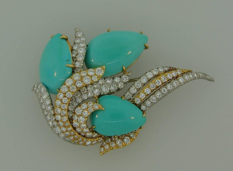 Stunning turquoise and diamond clip created by David Webb in the 1980s. It can also be worn as a pendant. Chic and elegant, the piece is a great addition to your jewelry collection.  The brooch is made of platinum and 18 karat yellow gold, features