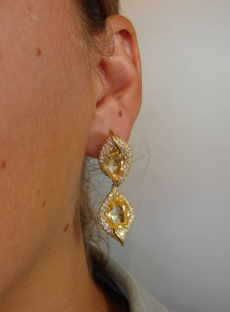 A pair of gorgeous earrings created by Henry Dunay in the 1980's.  Made of 18 karat (stamped) yellow gold and feature four briolette cut yellow sapphires accented with round brilliant cut diamonds. The yellow sapphires total weight is approximately