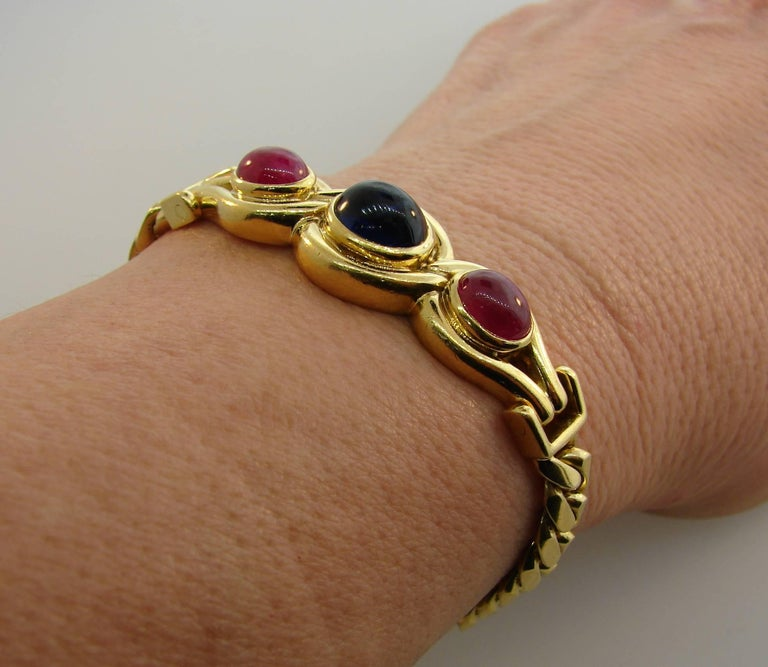 Bold yet elegant bracelet created by Bulgari in Italy in the 1980s. Chic and wearable, it is a great addition to your jewelry collection.  The bracelet is made of 18 karat yellow gold and set with an oval cabochon sapphire and two oval cabochon