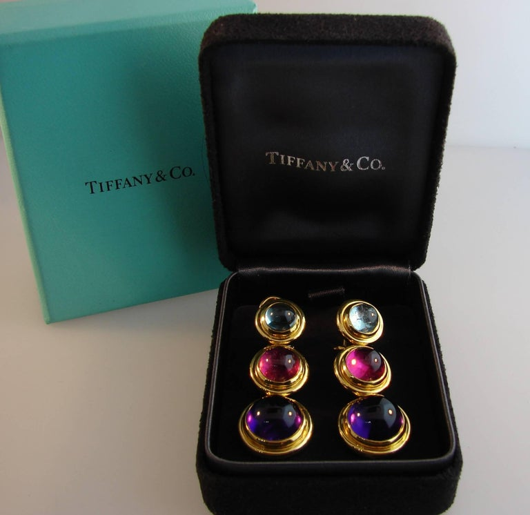 Chic colorful earrings created by Paloma Picasso for Tiffany & Co. Well proportioned, stylish and wearable, the earrings are a great addition to your jewelry collection.  Made of 18k yellow gold and set with cabochon amethyst, aquamarine and