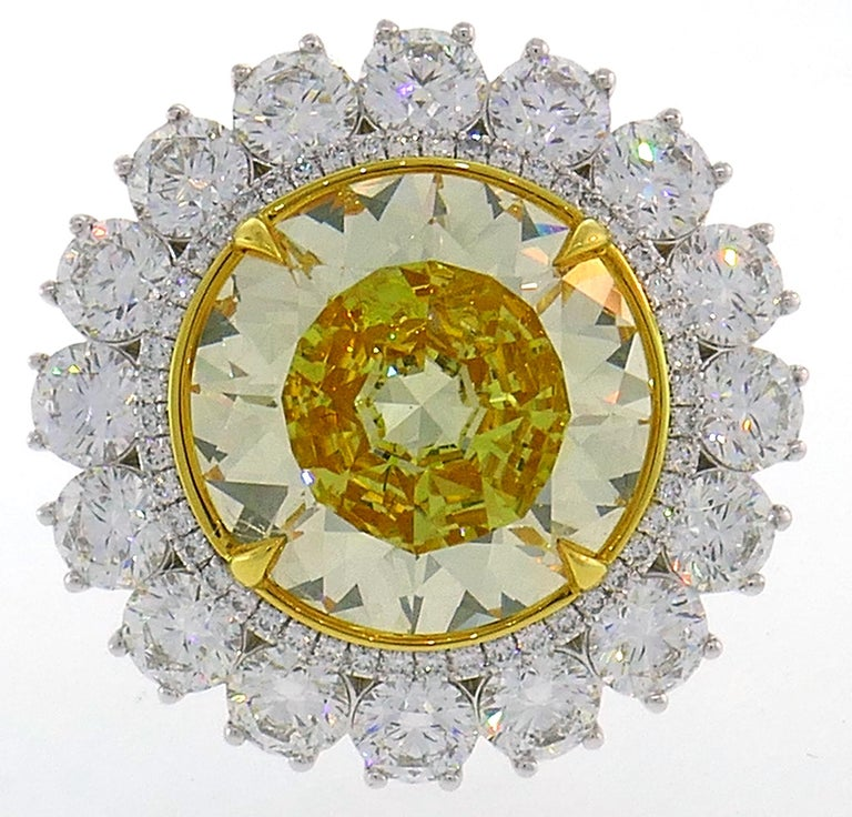 Magnificent fancy yellow diamond ring! Features a 10.04-carat natural fancy intense yellow round modified brilliant cut diamond framed by two rows of round brilliant cut white diamonds. The fancy yellow diamond comes with a GIA Colored Diamond