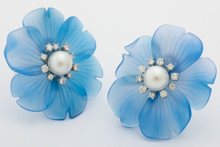 Beautifully carved in Germany, these blue onyx flowers are a soft cornflower blue. The center of the flower is accented with white diamonds , set in 14 kt white gold, with an 8 mm white Akoya pearl.