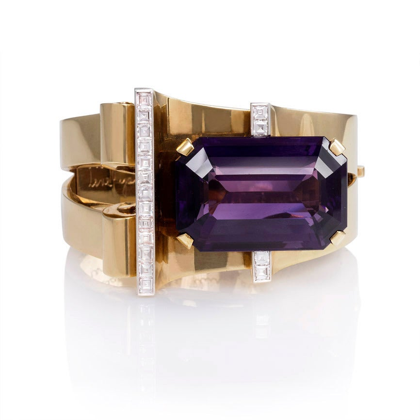 A Retro gold, amethyst, and diamond bangle bracelet, the open tapered front featuring curved and scroll motifs set with a large rectangular amethyst and square-cut diamond accents, in 14k.  Designed by MGM's Gilbert Adrian for Joan Crawford.