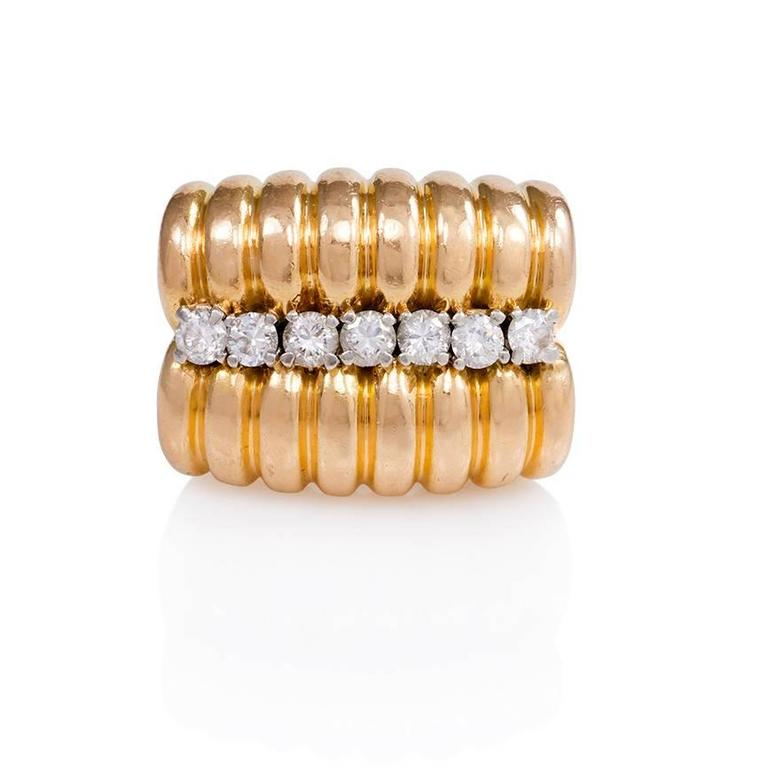 A Retro gold ring of ribbed two-row design with a central line of round modern brilliant cut diamonds and scrolled shoulders, in 18k.  French import.  Atw 0.75 ct.  Top measures 7/8