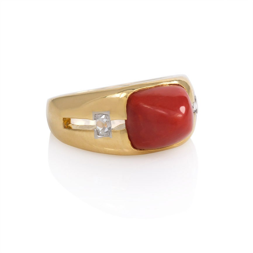 A Retro gold ring comprised of a central sugarloaf coral flanked by diamonds, in 18K. Janesich.