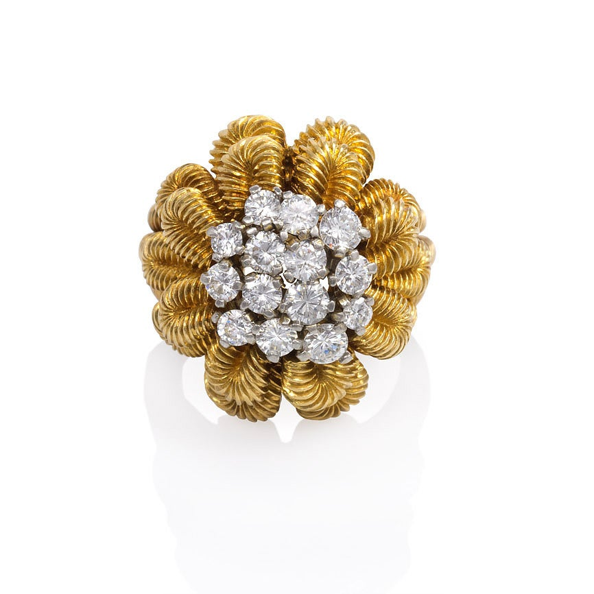 A ribbed gold and diamond cocktail ring in the form of a stylized flower with a diamond cluster center, in 18K and platinum.  Van Cleef & Arpels, France, #30493.