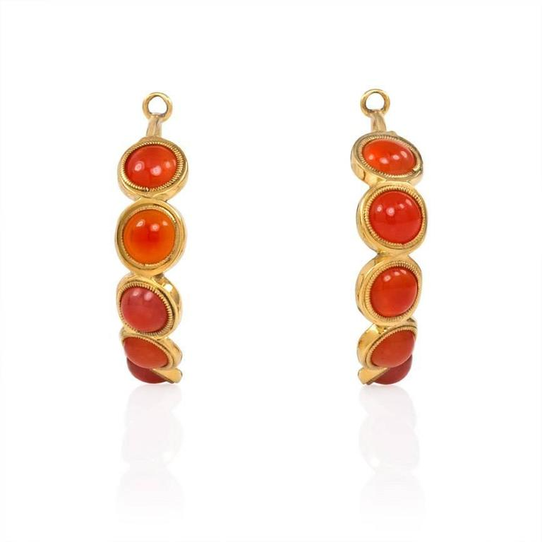 A pair of early Victorian gold and carnelian earrings of hoop design, each set with seven carnelian cabochons, in 15k.  England