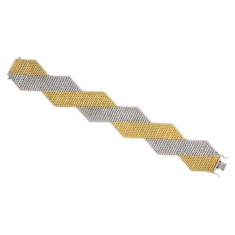 A woven two-color gold bracelet of geometric design with fabric-like texture, in 18k. Italy, Dutch import marks.
