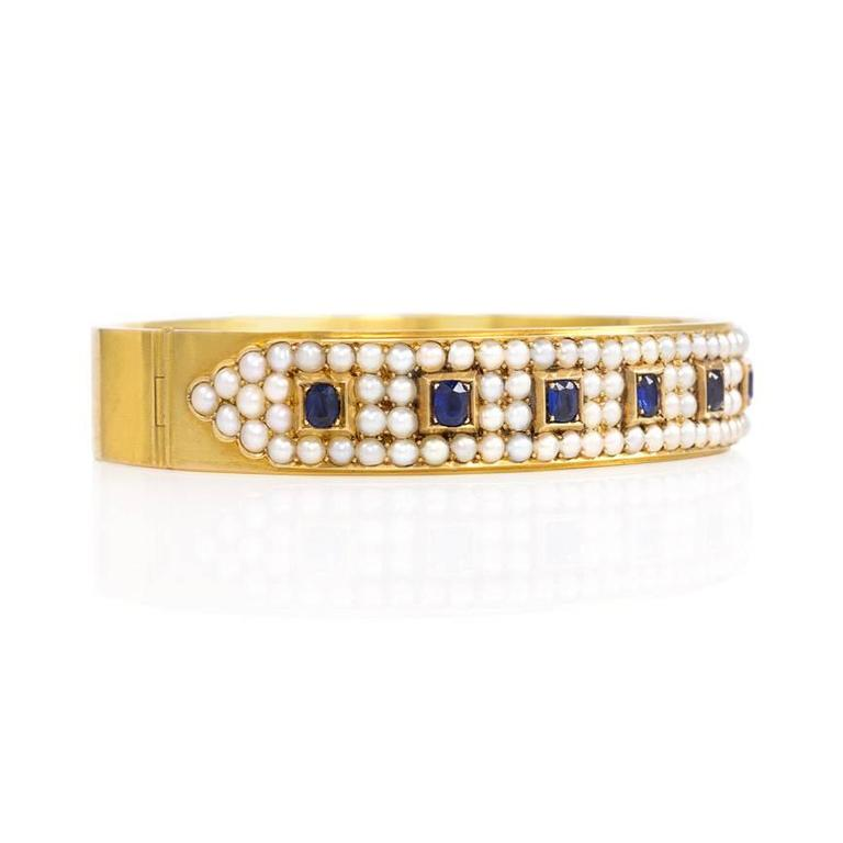 "An antique gold bangle bracelet of pavé half pearls and box-set cushion-cut sapphires, in 15k.  England.  Inner circumference measures approximately 6.25""."