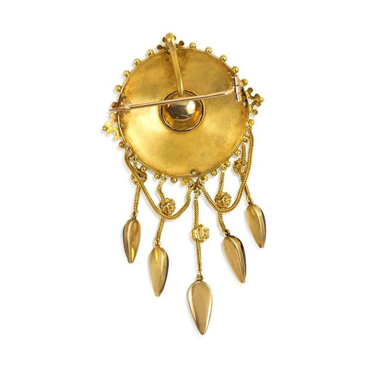 An antique gold and pearl circular pendant brooch with a central cabochon garnet supending chain swags and terminating in drop-shaped garnets, in 18k. France