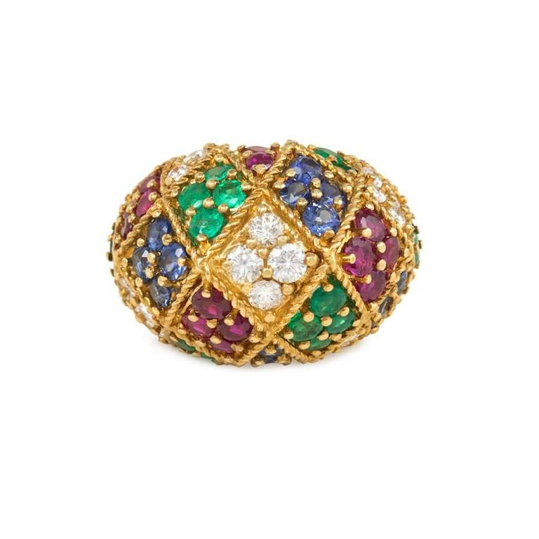 A textured gold bombé ring set with diamonds, rubies, sapphires, and emeralds in a harlequin motif, in 18k.  Top: 3/4in. high, 1in. wide
