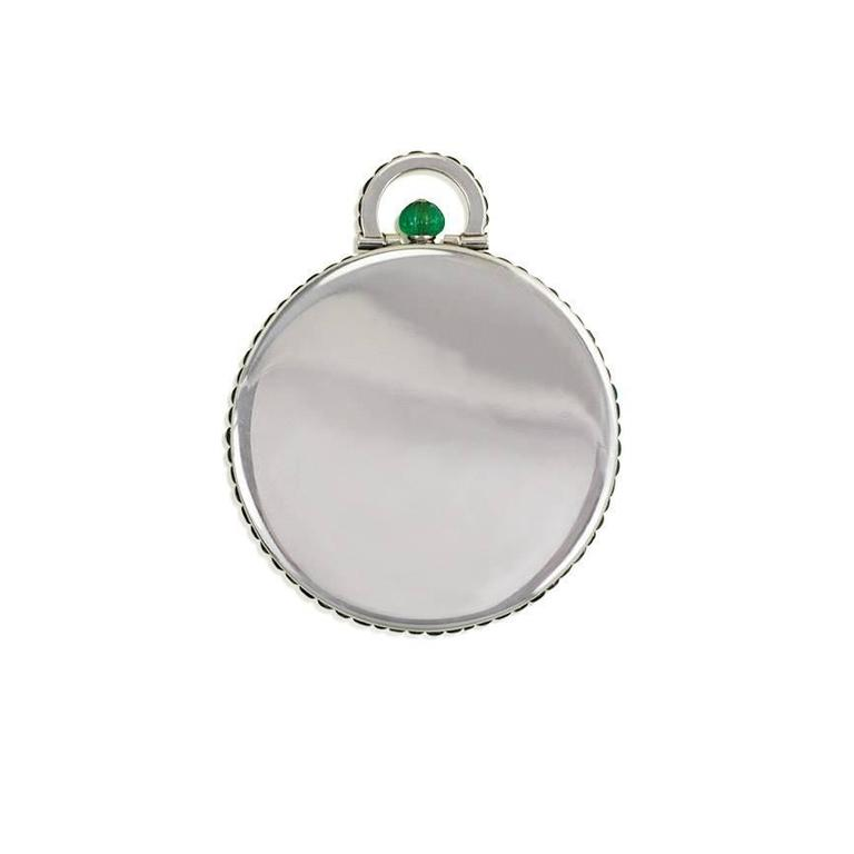 An Art Deco pendant pocket watch, the dial featuring diamond accented Roman numerals and a small seconds indication in the sub dial, with a carved emerald crown and cabochon emerald accents on the side case and bale, in platinum. Movement signed
