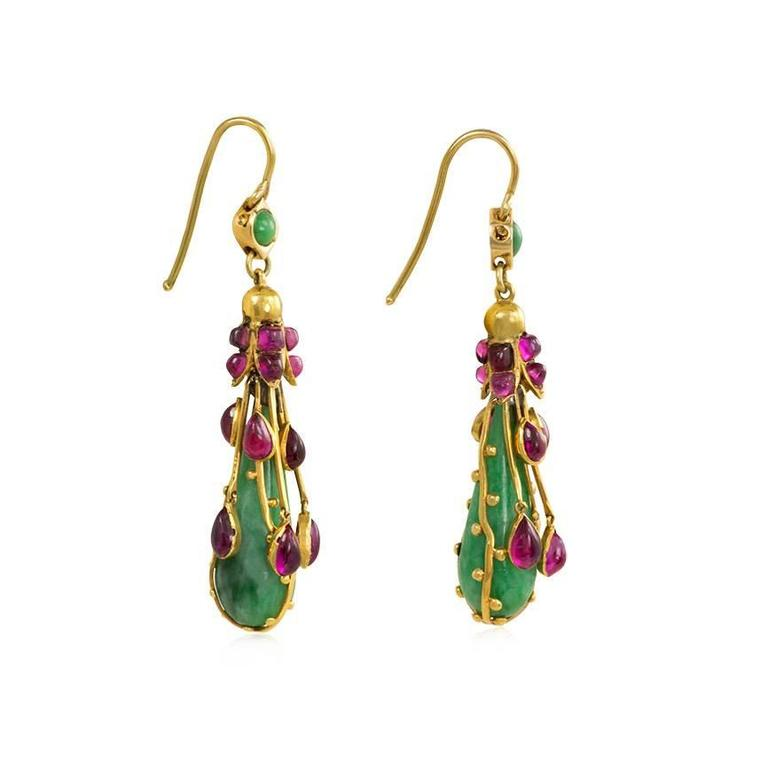 A pair of Art Nouveau gold, jade, and ruby earrings, the pear-shaped jade pendants suspending from gold foliate and cabochon ruby caps and decorated with gold wire and articulated cabochon ruby drops, in 15k.  England, Dutch import