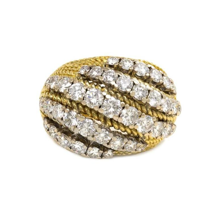 A gold and diamond bombé ring of striped design, in 18k and platinum. Mellerio, France. Atw. 3.00 tw. diamonds.  Current size: 7  Top measures approximately 11/16 x 15/16 inches