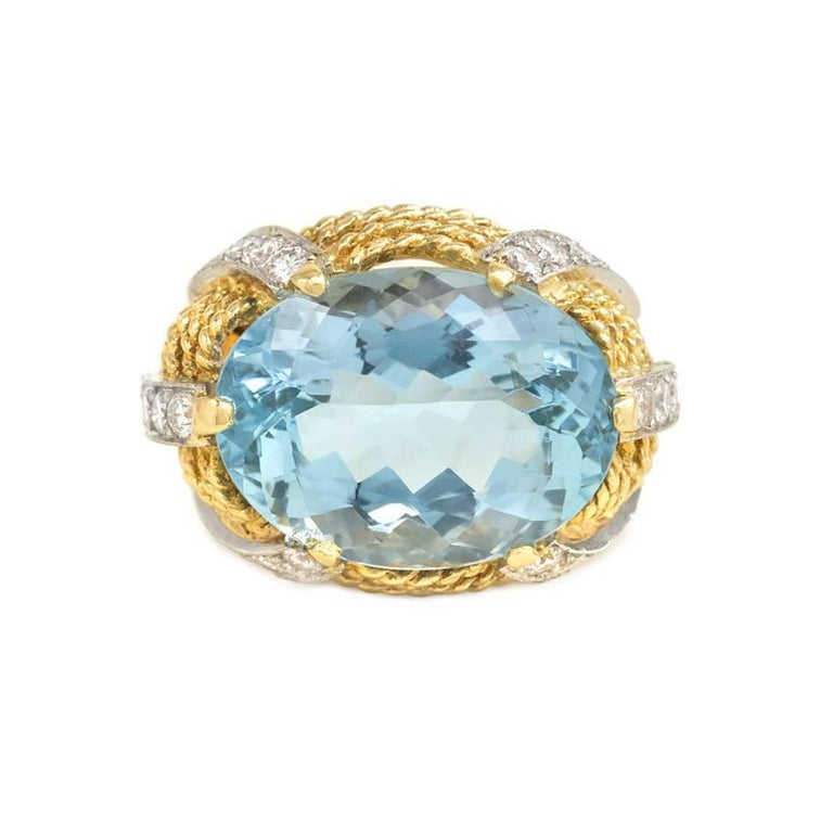 "An aquamarine cocktail ring in a rope twist gold setting with diamond embellishment, in 18k and platinum. Atw. 1.20 ct. diamonds; faceted aquamarine approx. 17.53 ct.  Top measures approx. 3/4"" wide"