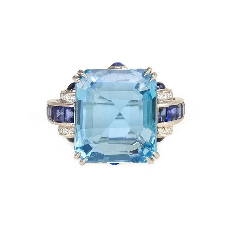 """A Retro aquamarine cocktail ring in a sapphire and diamond mounting with cabochon sapphire terminals accenting the open gallery, in platinum.  Atw aquamarine 10.38 cts.  Top of ring measures approx. 9/16 x 7/8"""""""