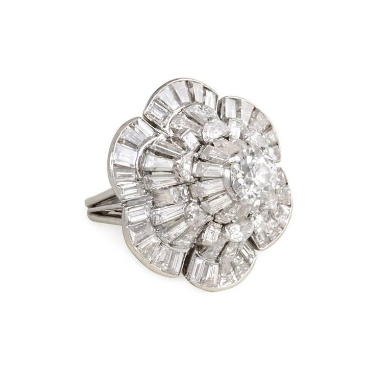 A structured diamond cocktail ring in the shape of a stylized flower, in platinum. Oscar Heyman Bros., #51677.  Approximate total weight 5.70 cts. round, baguette, and half moon shaped diamonds.  Dimensions: top measures 2.4 x 2.6 cm, sits about