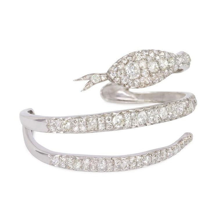 An Art Deco cuff bracelet comprised of old cut diamonds in the form of a coiled serpent, in platinum. France.  Atw. 9.52 cts.  Inner circumference approximately 6 3/4 inches