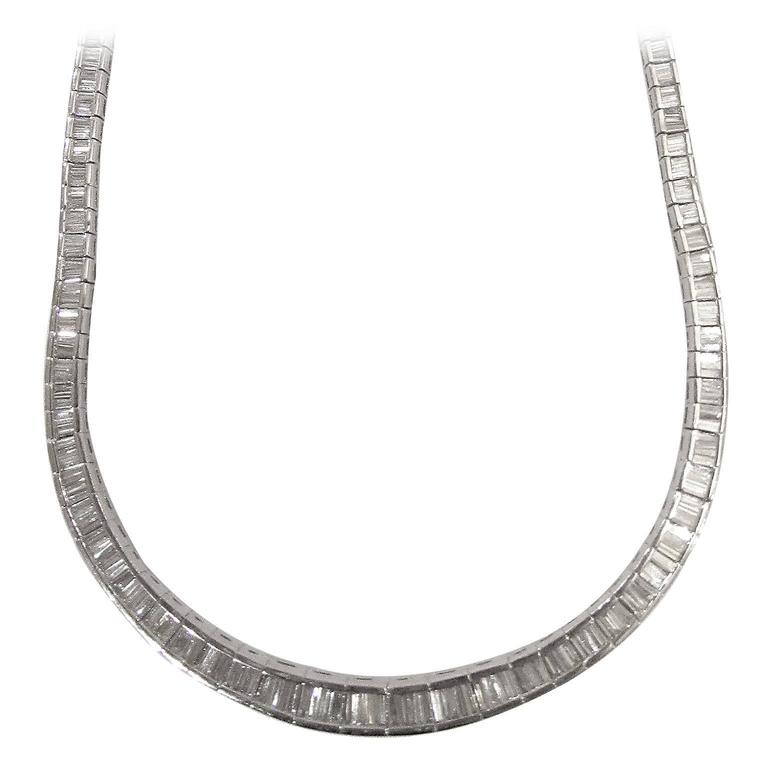 Platinum Riviera necklace sporting approximately 17 carats of F-G color,  VS1-VS2 grade tapered baguette-cut diamonds, in a flexible platinum mounting 45.44 DWT. Sits higher on neck for perfect viewing. This ice will warm the heart of any woman!