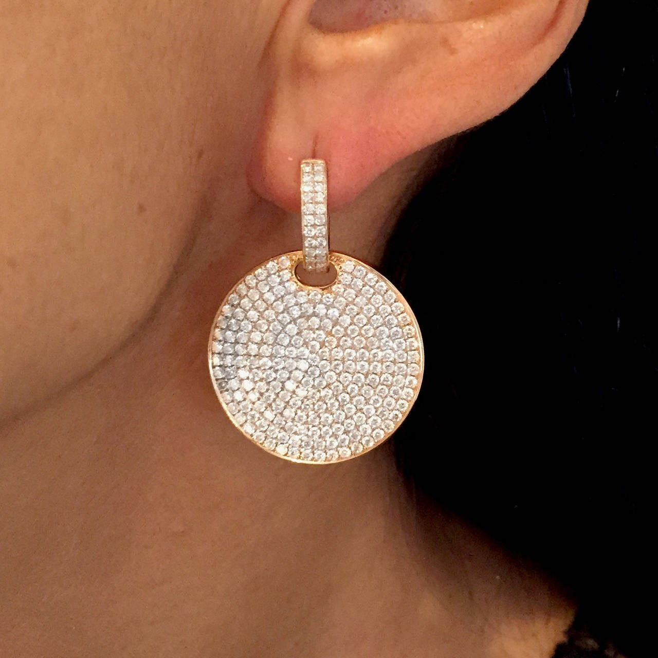 Contemporary disc-shaped earrings a full inch in diameter, inset with over 450 individual round-cut diamonds, for a total of 4.15 carats ... a sparkling accent to any formal evening.