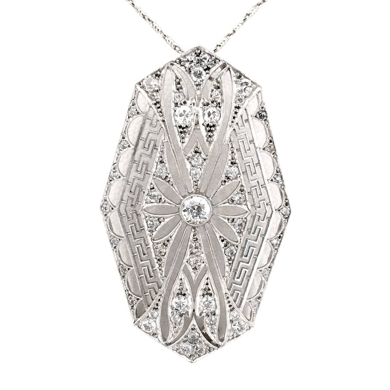 This original N-0025platinum Art Deco diamond pendant features a delicate and airy open-work design, including a dramatic Greek-key and floral filigree motif, all surrounding a one-carat diamond. 1-3/4 long, 1 inch wide. 16-inch 14k gold chain