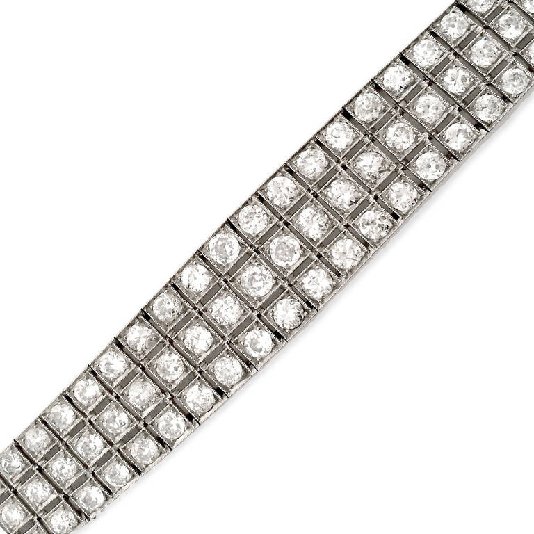 Wide Art Deco bracelet fully decked with 3 rows of old European cut  diamonds ( approx. 8 carats) in graduating sizes. Moves like liquid. Elegant platinum setting engraved on sides. G-H, VS2-SI2 7 inches long.