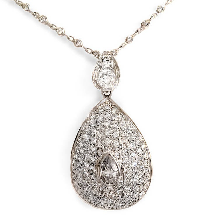 Teardrop pendant/brooch features central pear-shaped diamond surrounded by pavé-set brilliant-cut diamonds. Chain sold separately.