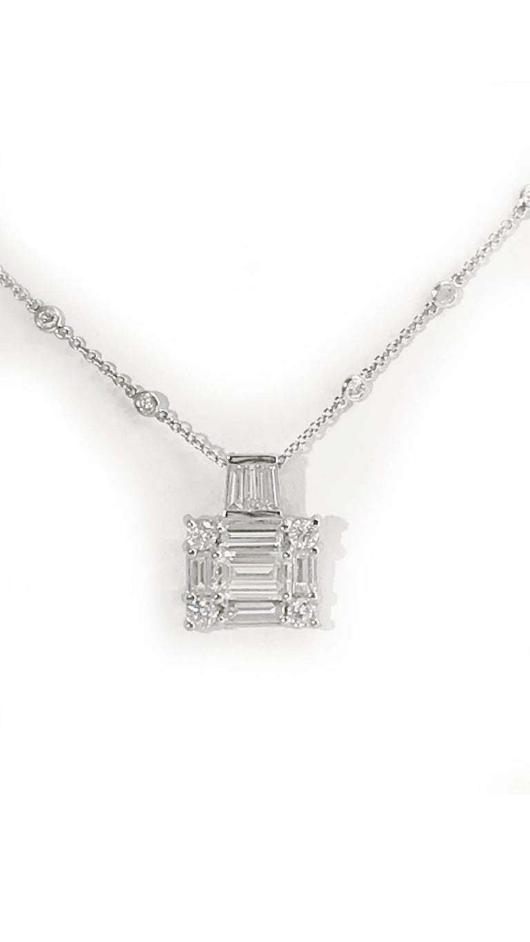 This is a custom mounting in 18k White Gold. Center Emerald cut Diamond is 2.00 carats J, VVS. Surrounding in an Art Deco inspired design 3.00 additional carats of Baguettes and Brilliant cut Diamonds. The custom bail consists of 3 large tapered