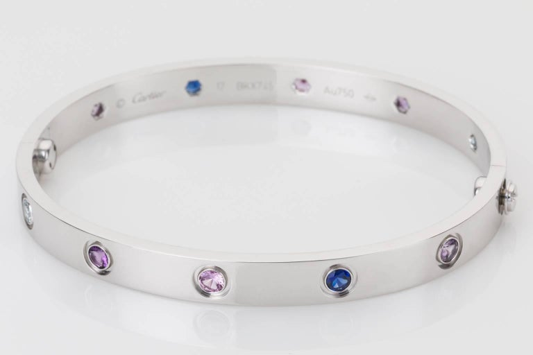 Contemporary, elegant & collectable this 18k white gold Cartier love bangle is set with a total of ten gorgeous gemstones,  two aquamarines, two pink sapphires, two blue sapphires, two purple spinels and two amethysts and comes complete with the