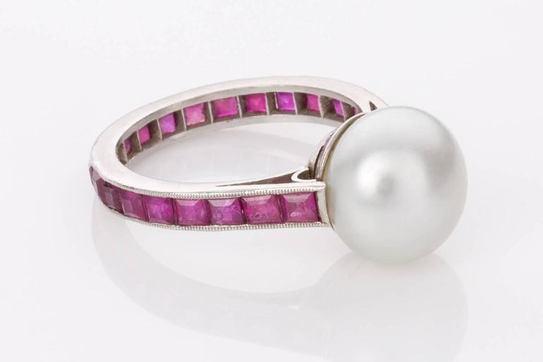 This unique estate Australian South Sea Pearl and Ruby dress ring is such a fabulous piece, so eye-catching and unusual. Featuring at the centre one 10-10.5mm button shape South Sea pearl with silver overtones and a bright lustre. The platinum band